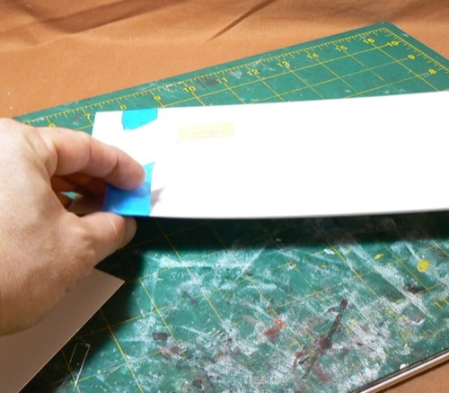 Photograph of taping Bristol Board to the  corrugated HO scale styrene roofing former sheet